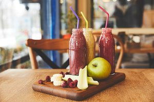 Fruits and smoothies in bottles on t
