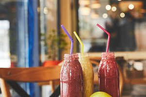 Bottles with fruit smoothies on tabl