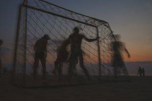 Football on a sandy beach at sunset