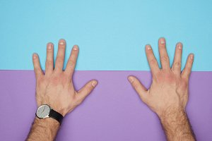 cropped shot of male hands on blue a
