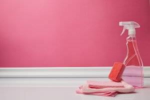 pink washing sponge, rags and spray