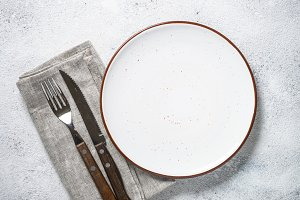 White plate and cutlery on stone