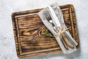 Wooden plate and cutlery on stone