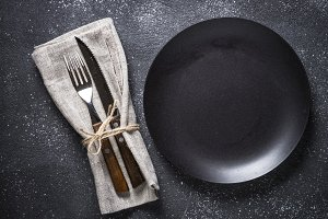 Black plate, cutlery and napkin on