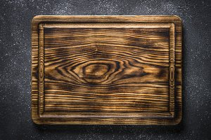Wooden cutting board on black top