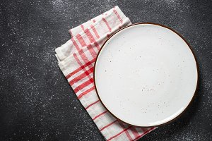 Empty white plate on dark stone