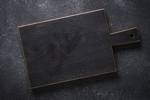 Black wooden cutting board on black