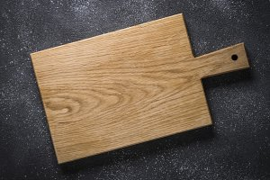 Empty wooden cutting board on black