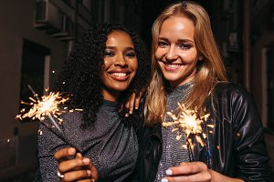 Smiling girls with sparklers