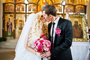 The kiss of wedding couple at church