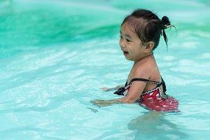 Happy baby Asian girl in swimming po