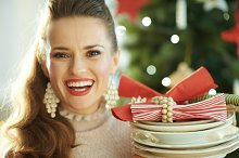 smiling housewife near Christmas tre