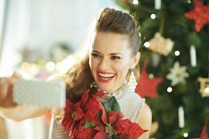 smiling woman with red poinsettia ta
