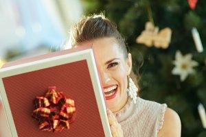 housewife near Christmas tree hiding