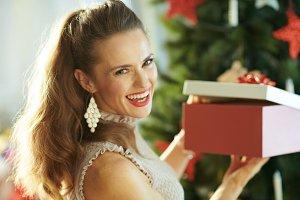 happy modern woman near Christmas tr