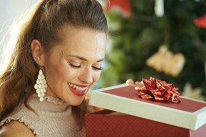 woman near Christmas tree looking in