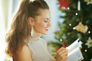 happy trendy housewife writing in di