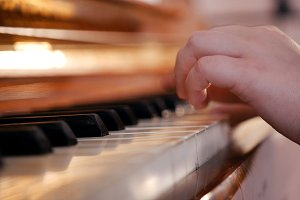 A baby hands playing piano on music