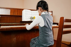 A little girl playing piano. Back