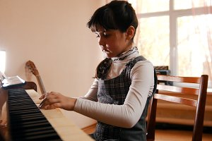 A little girl playing piano on music