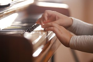 A little girl hands playing piano on