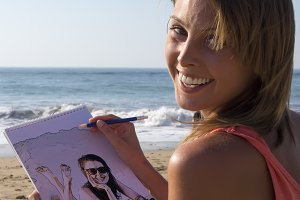 Woman drawing her sister at beach