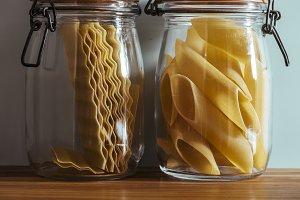 Glass jars with raw pasta, on the ki