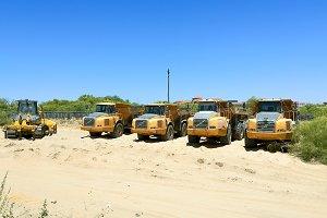Dump trucks and yellow bulldozer