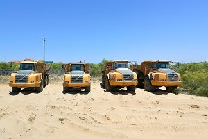 Dump trucks parked in the sand ready