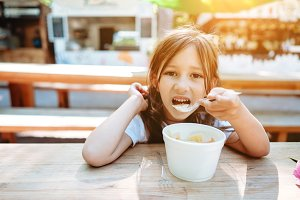 Little girl eating ice cream at a ca