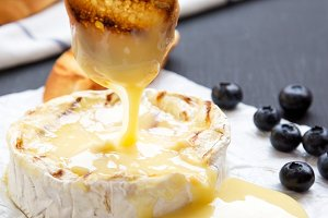 Grilled camembert cheese, side view.