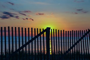 Sunset with wooden fence and ocean