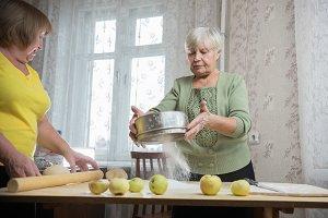 Two elderly woman making little pies