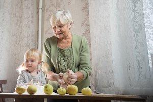An elderly woman making apple little