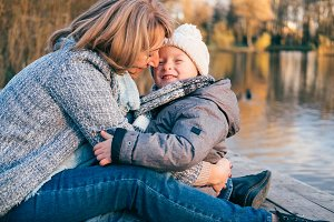 Mother and child hugging near lake