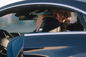 Image of woman in sunglasses in car