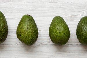 Whole avocados on white wooden