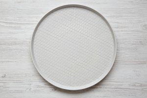 Grey round plate on white wooden