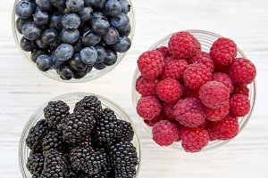 Three bowls containing berries.