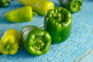Green peppers on the blue wooden bac