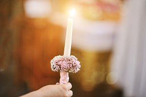 Burning candle at hand of bride on w