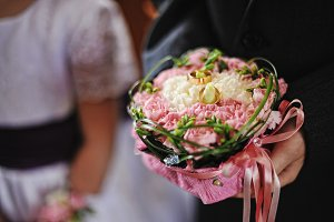 Wedding rings on bouquet at hand of