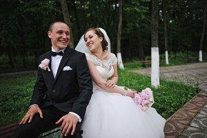 Cheerful wedding couple sitting on b
