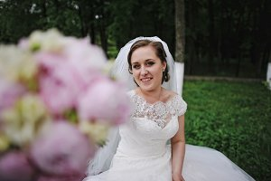 Beautiful bride showing peonies wedd
