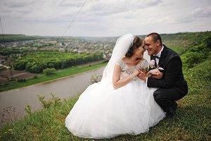 Gorgeous wedding couple sitting on t
