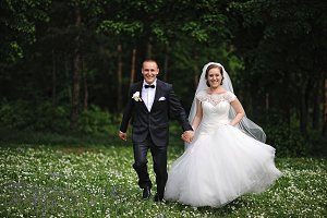 Happy newlyweds running at field of
