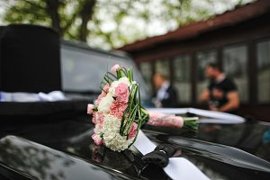 Wedding bouquet on the hood of car w