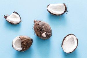 Fresh coconut halves on a blue bac