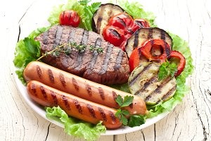 Grilled meat and vegetables over gre