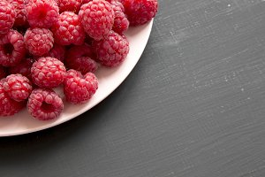 Raspberry on a pink plate on black